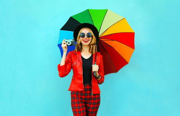 Happy smiling woman holding colorful umbrella, retro camera taking picture in red jacket, black hat on blue wall background stock photo