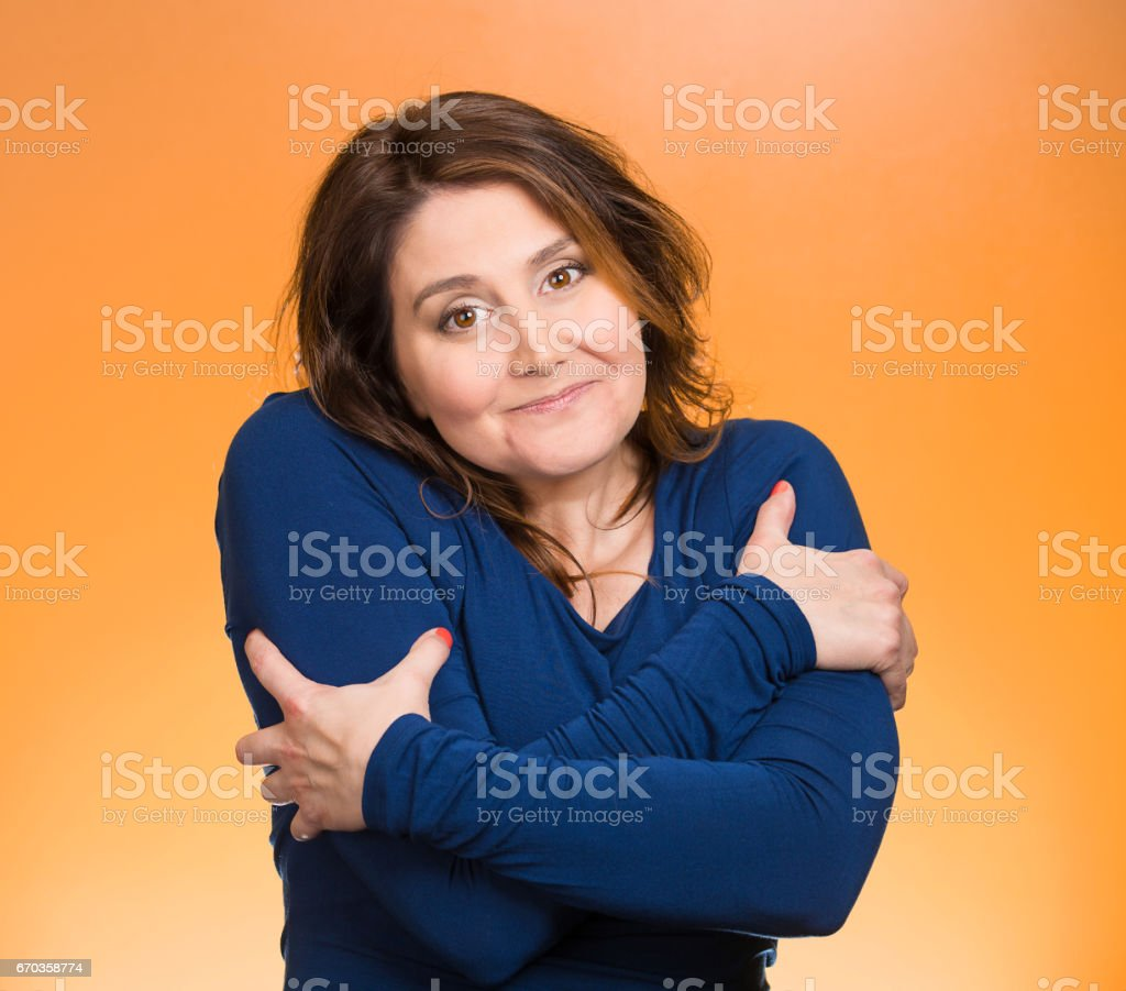 happy smiling woman, holding, hugging herself stock photo