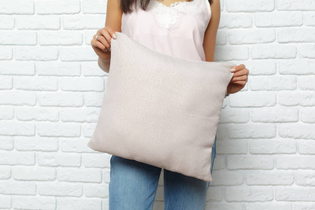 Happy smiling woman holding pillow Happy smiling woman holding pillow cushion stock pictures, royalty-free photos & images