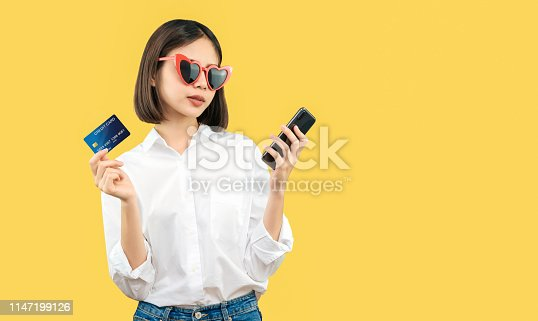 istock Happy smiling woman holding smart phone and credit card with shopping online. copy space for put advertisement. 1147199126