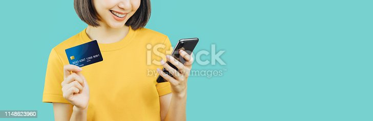 istock Happy smiling woman holding smart phone and credit card with shopping online. copy space for put advertisement. 1148623960
