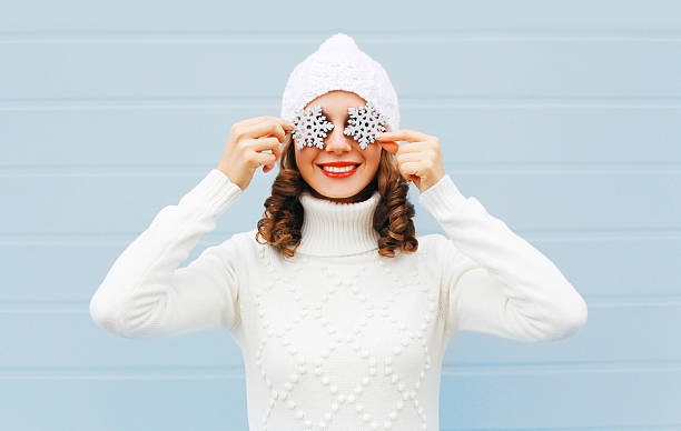 Happy smiling woman in knitted hat sweater with snowflakes stock photo
