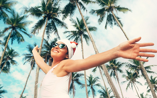 istock Happy smiling woman in Santa hat stay under palm trees. Christmas holiday on tropical island 1029251654