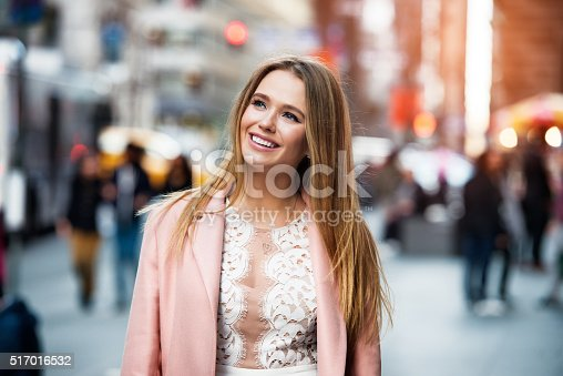 istock Happy smiling woman looking up and walking on city street 517016532