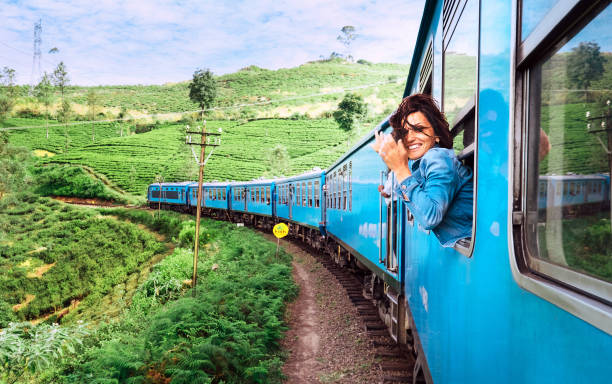Happy smiling woman looks out from window traveling by train on most picturesque train road in Sri Lanka stock photo