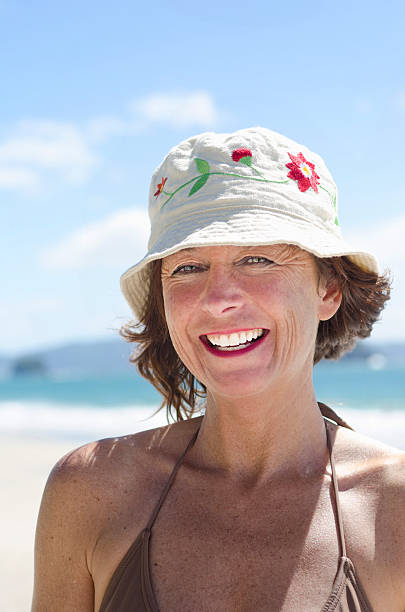 happy smiling woman on beach color portrait of a happy smiling mature woman in her forties wearing a summer hat and looking at the camera during a day out at the beach. middle aged women in bikinis stock pictures, royalty-free photos & images