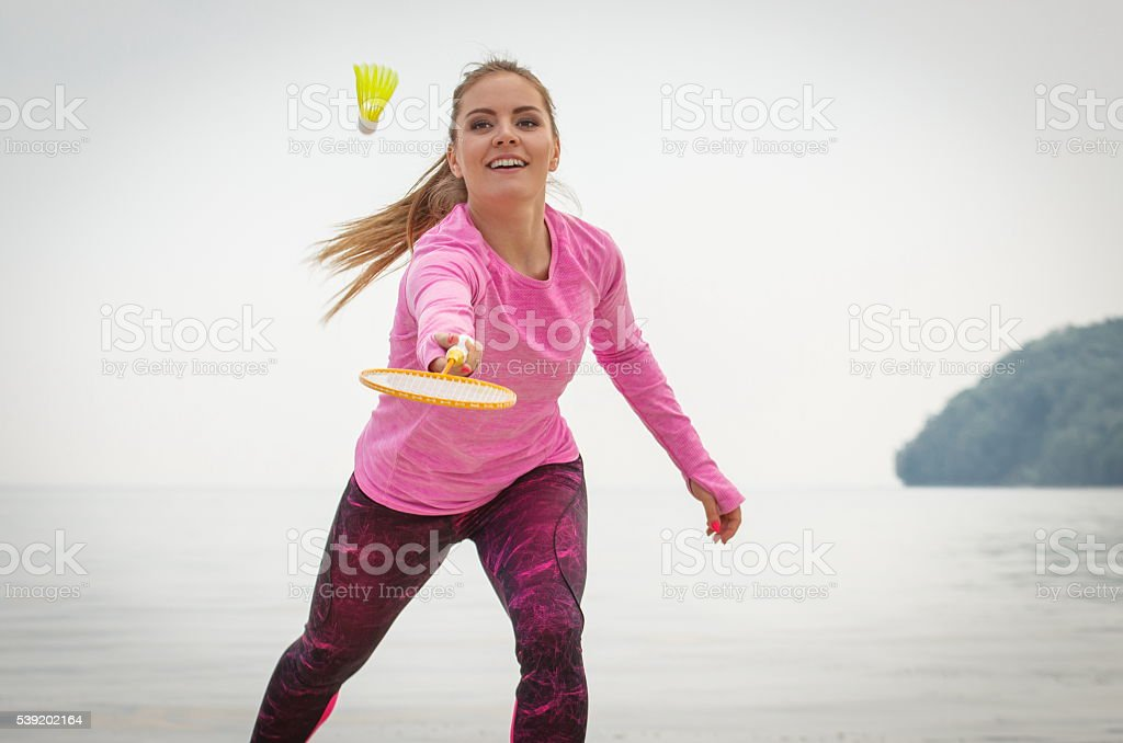 Happy smiling woman playing badminton at beach, active lifestyle stock photo