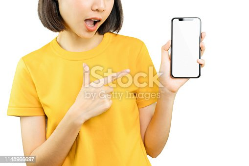 istock Happy smiling woman pointing with hand and finger to smart phone with amazed for success. copy space for put advertisement. 1148966697
