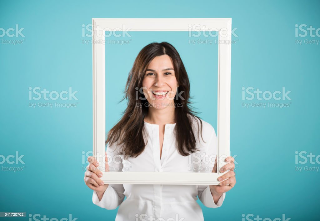 happy smiling woman posing with a picture frame stock photo