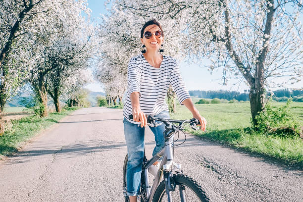 Happy smiling woman rides a bicycle on the country road under blossom trees. Spring is comming concept image. Happy smiling woman rides a bicycle on the country road under blossom trees. Spring is comming concept image. springtime stock pictures, royalty-free photos & images