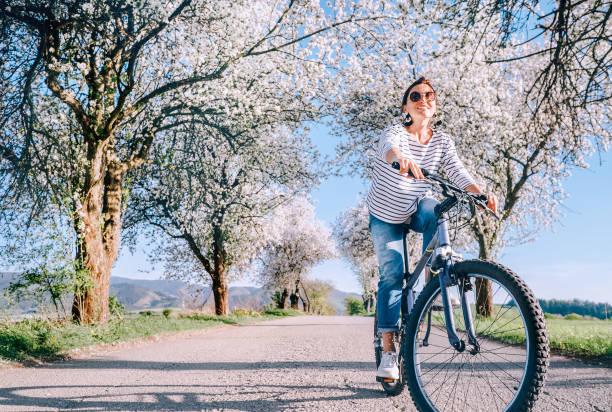 Glücklich lächelnde Frau fährt Fahrrad auf der Landstraße unter blühenden Bäumen. Der Frühling kommt Konzept Bild. – Foto