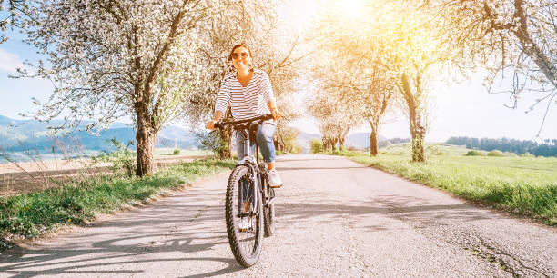 Glücklich lächelnde Frau fährt ein Fahrrad auf der Landstraße unter Blütenbäumen. Frühling kommt Konzeptbild. – Foto