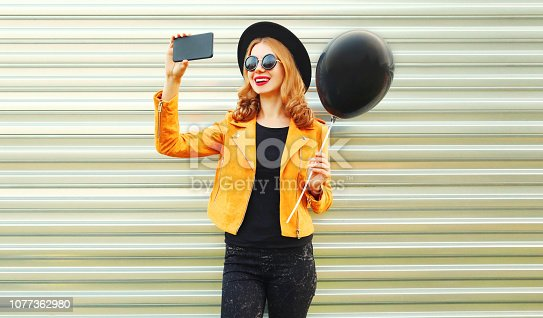 istock happy smiling woman taking selfie picture by smartphone holding black helium air balloon in round hat, yellow jacket on metal wall background 1077362980
