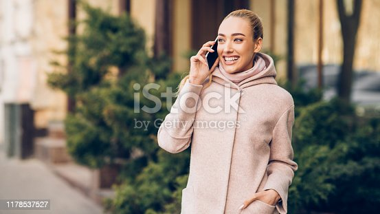 Happy smiling woman talking on cellphone outdoors in city, enoying walk at autumn day