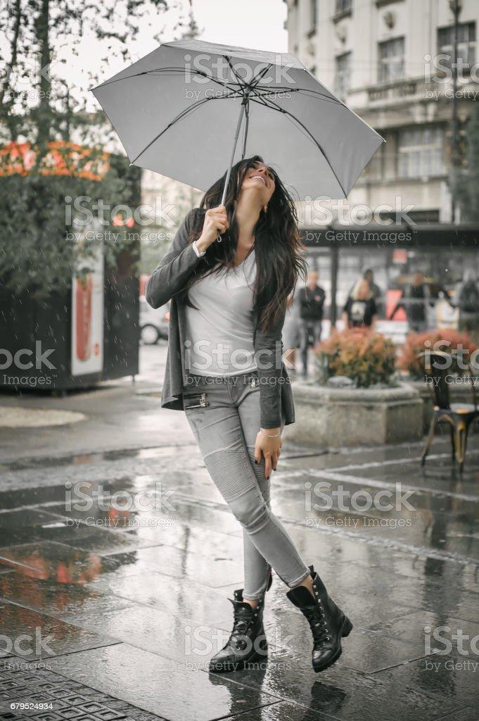 Happy smiling woman under umbrella in rain royalty-free stock photo