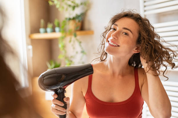 Happy smiling woman using hair dryer in bathroom stock photo