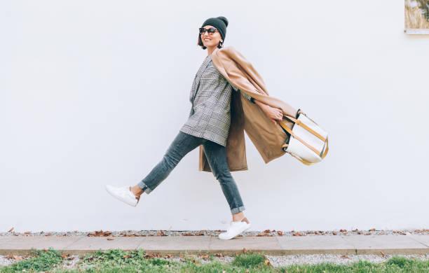 glücklich lächelnde frau fuß auf der straße. vielschichtigen stil mode outfit - handtasche jeans stock-fotos und bilder