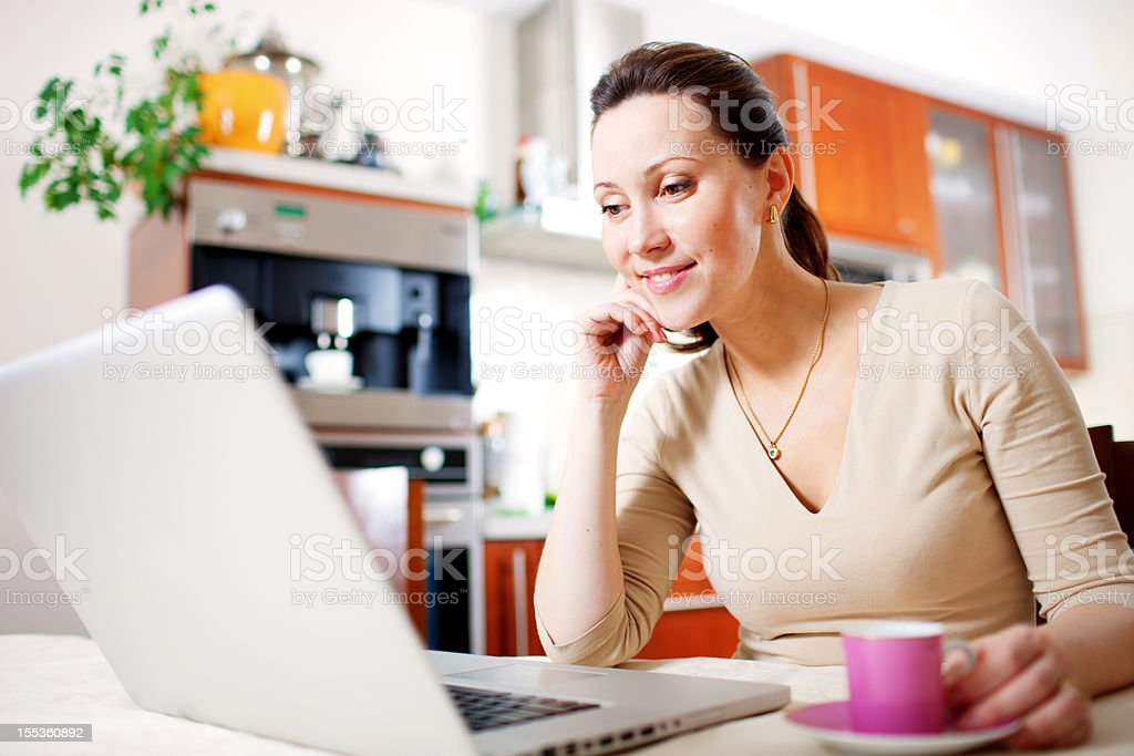 Happy Smiling Woman with Laptop and Coffee in the kitchen royalty-free stock photo