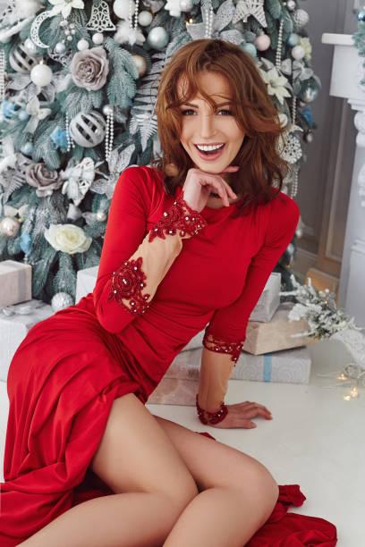 5a76359f4 Feliz sonriente mujer en un vestido de noche largo rojo sentado cerca de  árbol de Navidad