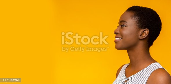 Happy smiling african american girl profile portrait. Black woman looking aside at copy space