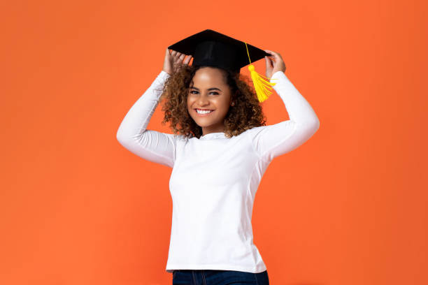 Happy smiling young African American woman wearing graduation cap stock photo