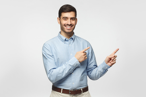 istock Happy smiling young business man pointing away, isolated on gray background 1093999852