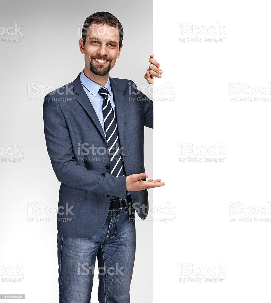 Happy smiling young businessman showing large blank signboard royalty-free stock photo