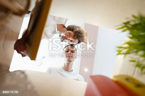 istock Happy smiling young couple opening an unpacked carton box and looking inside 836473730