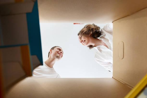 glücklich lächelnd junges paar ein ausgepackt karton öffnen und blick ins innere - kinder verpackung stock-fotos und bilder