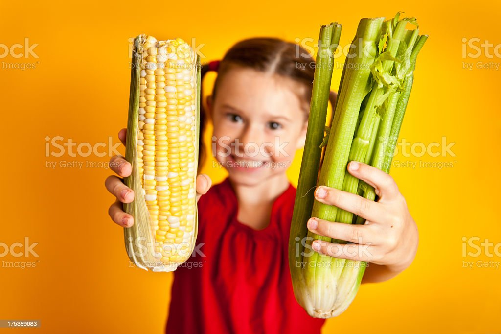 Happy, Smiling, Young Girl Holding Celery and Corn royalty-free stock photo