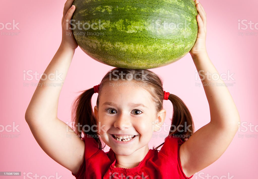 Happy, Smiling, Young Girl Holding Watermelon Above Her Head stock photo