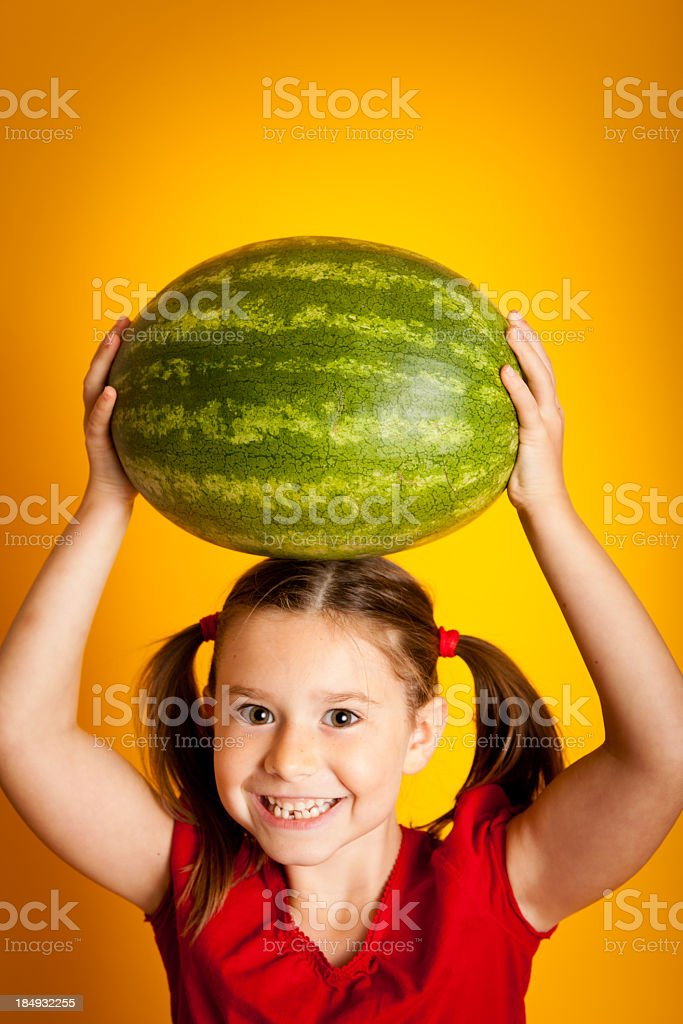 Happy, Smiling Young Girl Holding Watermelon Above Her Head royalty-free stock photo