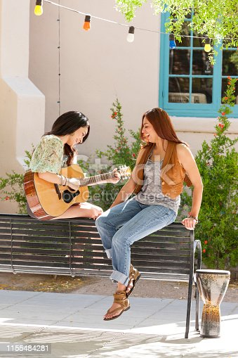Happy, smiling, young Hispanic women friends having fun together outdoors in a city park. One woman is playing guitar.