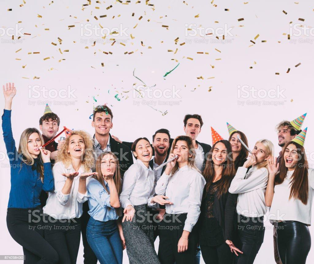 幸せのギフト用の箱を持つ若い人々 を笑顔でパーティー ホイッスルを吹きます。 ストックフォト