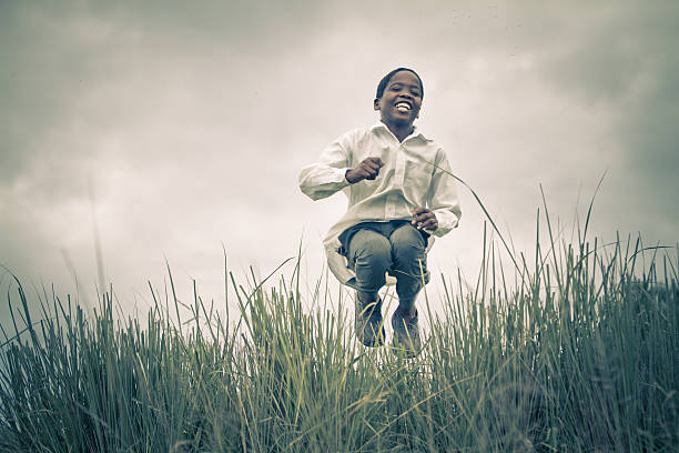 happy smiling young south african boy - african youth jumping for joy stock photos and pictures