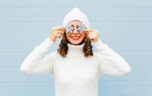 Happy smiling young woman in knitted hat and sweater with snowflakes on face having fun over blue background stock photo