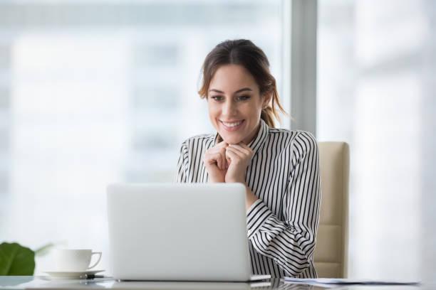 felice donna sorridente giovane guardando lo schermo del laptop. - incentivo foto e immagini stock
