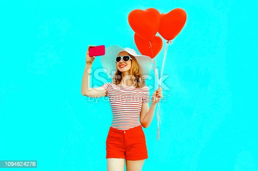 istock Happy smiling young woman taking selfie picture by phone with red heart shaped air balloons in summer straw hat and shorts on colorful blue background 1094624276