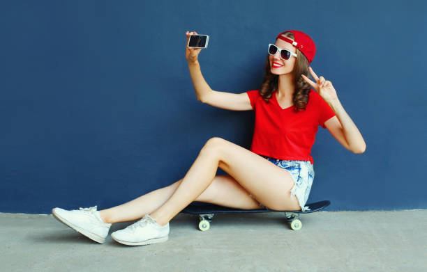Happy smiling young woman taking selfie picture by smartphone sitting on skateboard wearing red baseball cap, shorts on city street over blue wall background stock photo