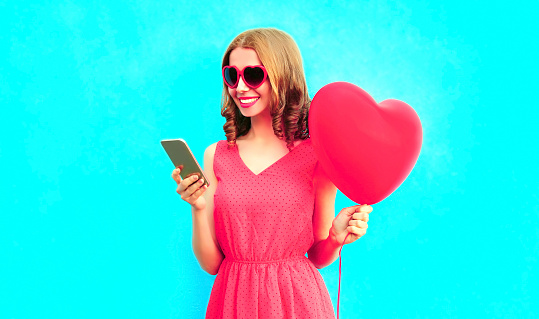 istock Happy smiling young woman with phone, pink heart shaped air balloons on colorful blue background 1130327328