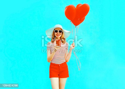 istock Happy smiling young woman with phone, red heart shaped air balloons in summer straw hat and shorts on colorful blue background 1094624266