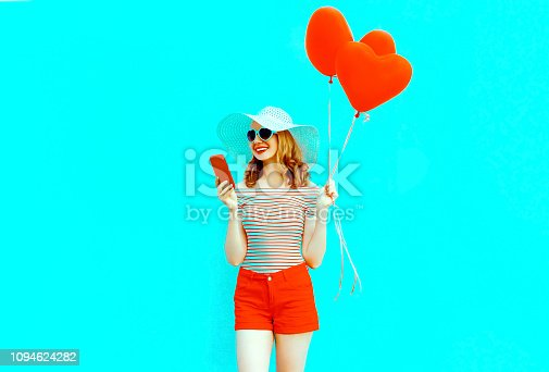 istock Happy smiling young woman with phone, red heart shaped air balloons in summer straw hat and shorts on colorful blue background 1094624282
