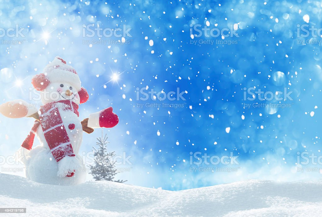 Happy snowman standing in winter christmas landscape stock photo