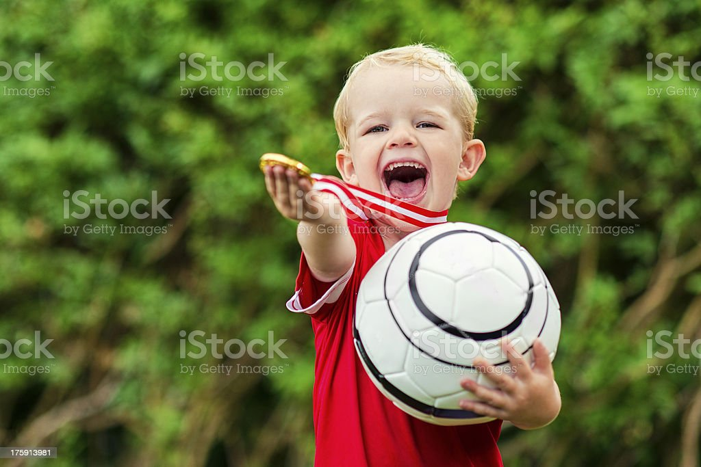 Happy soccer boy is proud of a gold medal royalty-free stock photo