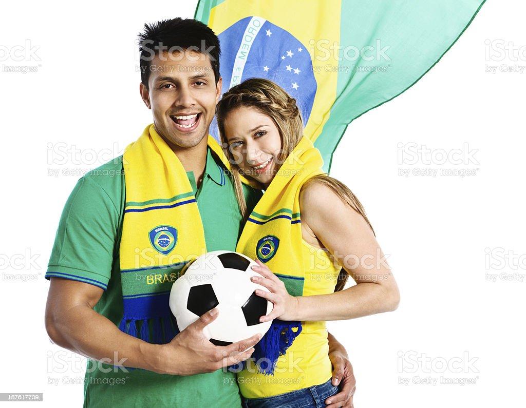 Fã de futebol casal feliz abraçando na frente da Bandeira Brasileira - foto de acervo