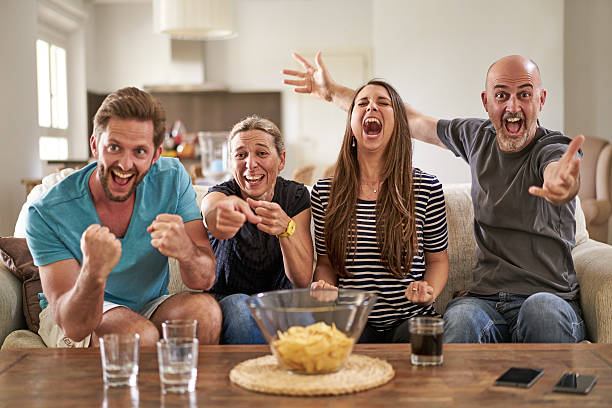 happy soccer fans cheering their team on tv - sports championship stock photos and pictures