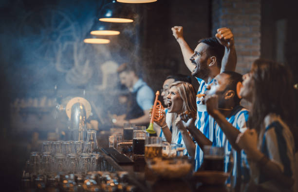 happy soccer fans cheering while watching a game in a bar. - sports event stock photos and pictures