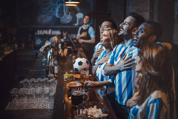 happy soccer fans singing the anthem before the game in a bar. - national anthem stock photos and pictures