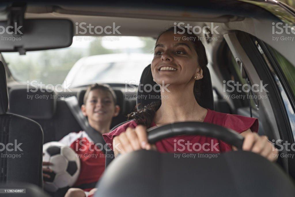 Glücklich Fußball-Mama Kind zum Fußballtraining in ihrem Auto transportieren – Foto