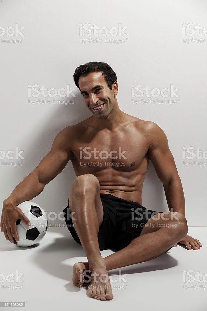 Happy soccer player leaning against a wall royalty-free stock photo